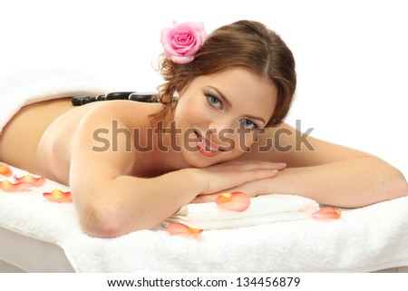 beautiful young woman in spa salon with spa stones, isolated on white - stock photo