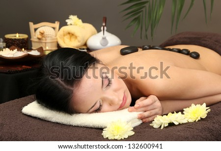 Beautiful young woman in spa salon with spa stones, on dark background - stock photo