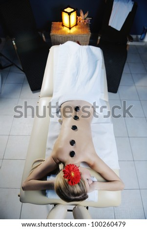 Beautiful young woman in spaand wellness. Face back and  stone massage - stock photo