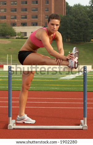 Beautiful Young Woman in Sports Bra and Shorts Stretching Hamstring on Hurdle