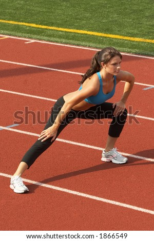 Beautiful Young Woman in Sports Bra Doing Leg Lunge - stock photo