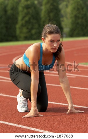Beautiful Young Woman in Sports Bra in Starting Position - stock photo