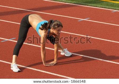 Beautiful Young Woman in Sports Bra Leaning Forward and Stretching Hamstrings - stock photo