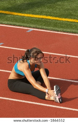 Beautiful Young Woman in Sports Bra Stretching Hamstring on Track - stock photo