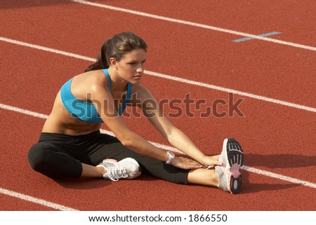 Beautiful Young Woman in Sports Bra Stretching Leg on Track - stock photo