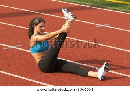 Beautiful Young Woman in Sports Bra Stretching Raised Leg on Running rack - stock photo