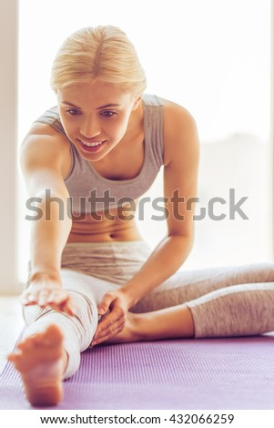 Beautiful young woman in sports wear is smiling while stretching on a yoga mat