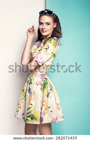 beautiful young woman in spring flower pattern dress, sunglasses, high heels. Fashion photo - stock photo