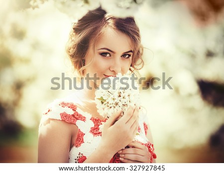 Beautiful young woman in spring garden - stock photo
