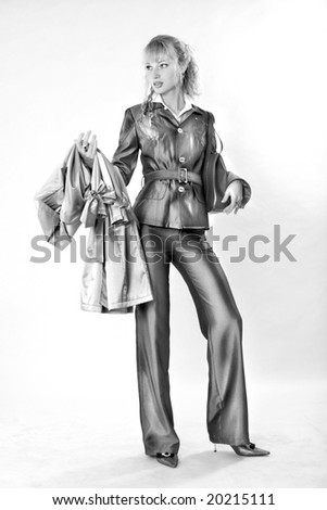 Beautiful Young Woman in suit. With bag and coat. In all growth. In the studio