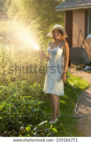 Beautiful young woman in summer dress enjoying watering garden with hose - stock photo