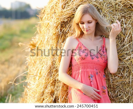 Beautiful young woman in summer dress standing in field, nature - stock photo