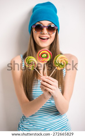 Beautiful young woman in sunglasse is holding lollipops and smiling while standing against grey background. - stock photo