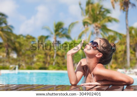 Beautiful young woman in sunglasses blowing air kiss in luxury pool