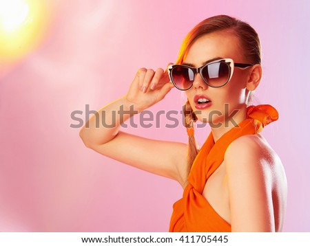 Beautiful young woman in sunglasses posing on the light colored spotlights.sunny summer teen girl