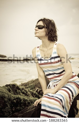Beautiful young woman in sunglasses sitting on stone on the empty beach at coastline of Sri Lanka, Ceylon. Vertical image with vintage filter