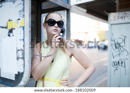 Beautiful young woman in sunglasses standing chatting on a public pay phone in a booth at the side of an urban street