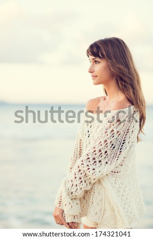Beautiful young woman in sweater on the beach at sunset, Fashion lifestyle warm backlit sunlight - stock photo