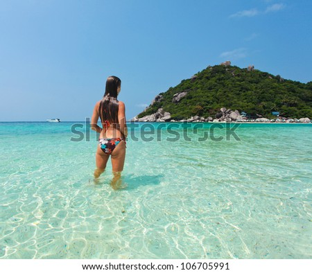 Beautiful young woman in swimsuit is in the water at the seashore. View from the back - stock photo