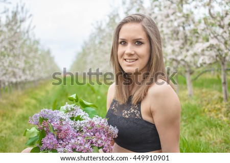 beautiful young woman in the apple garden on a warm summer day - stock photo
