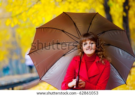 beautiful young woman in the autumn park with umbrella