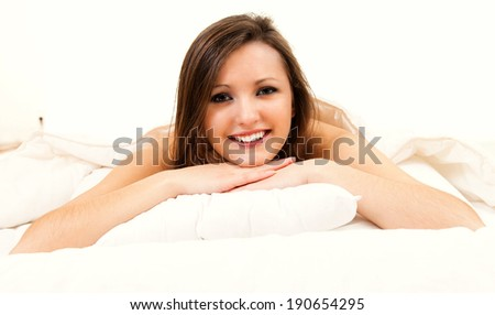 beautiful young woman in the bed, smiling - stock photo