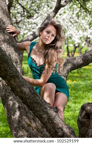 Beautiful young woman in the blossoming garden
