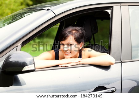 beautiful young woman in the car, smiling - stock photo