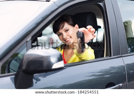beautiful young woman in the car, with key  - stock photo