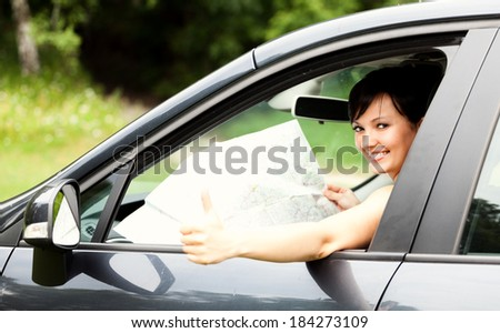 beautiful young woman in the car, with map  - stock photo