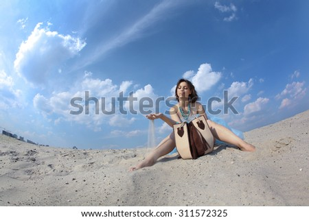 Beautiful young woman in the desert in a long blue dress on a background of blue sky, shot for the magazine, fashion, style, summer, - stock photo