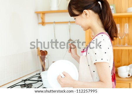 Beautiful young woman in the kitchen. Portrait of asian. - stock photo