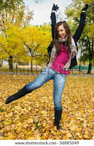 Beautiful young woman in the park at autumn - stock photo
