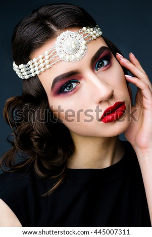 Beautiful young woman in the studio on a black background in the plan in the style of the 20s, vintage, closeup portrait with red lips
