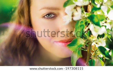 beautiful young woman in the summer park, near the apple tree with flowers, closeup  - stock photo