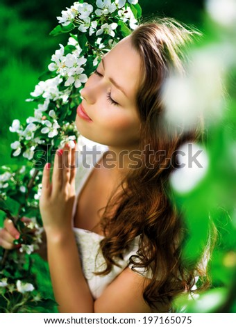 beautiful young woman in the summer park, standing near the apple tree with flowers - stock photo