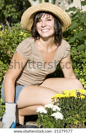 Beautiful young woman in the yard gardening - stock photo
