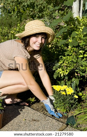 Beautiful young woman in the yard gardening - stock photo