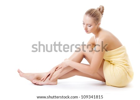 Beautiful young woman in towel sitting on the floor and stroking her beauty legs - stock photo