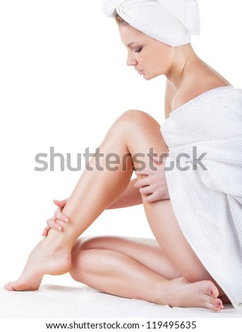 Beautiful young woman in towel sitting on the floor and stroking her legs isolated on white background - stock photo