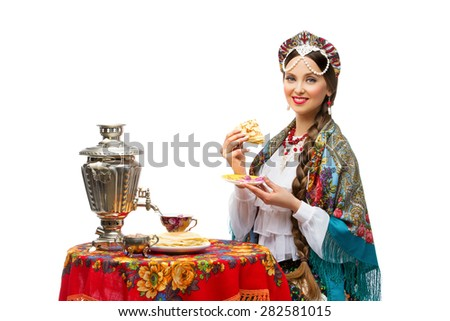 Beautiful young woman in traditional Russian costume sitting in front of table with pancake in her hand. Isolated - stock photo