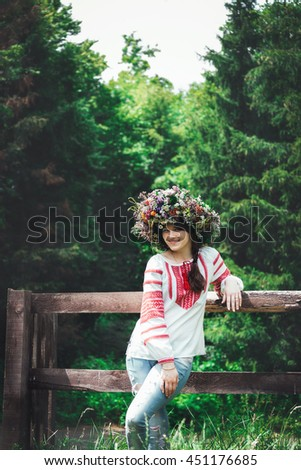 beautiful young woman in traditional Ukrainian costume and a large floral wreath stands near a wooden fence in a forest and looking at the camera - stock photo