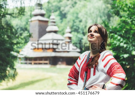 beautiful young woman in traditional Ukrainian costume stands on the background of a wooden big church. - stock photo
