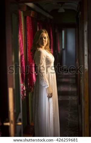 Beautiful young woman in vintage dress posing at old train - stock photo