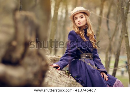Beautiful young woman in vintage purple dress and white hat sitting on rocks in the park in early spring, reverie, daydreaming, - stock photo