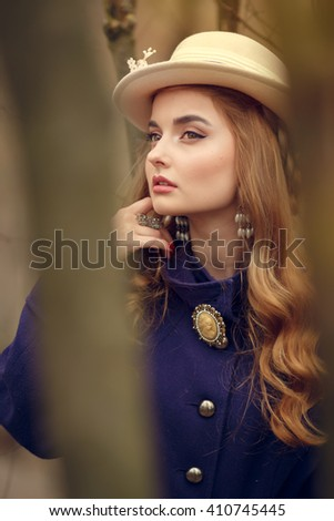 Beautiful young woman in vintage purple dress and white hat walks in the park in early spring, behind the trees, reverie, daydreaming, - stock photo