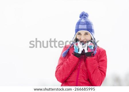 Beautiful young woman in warm clothing walking outdoors - stock photo