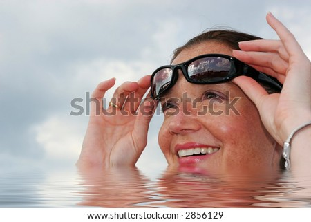 beautiful young woman in water lifting sunglasses; smiling - stock photo