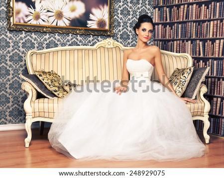 beautiful young woman in wedding dress sitting on sofa - stock photo