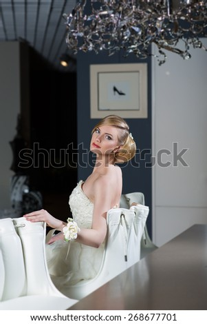 Beautiful young woman in wedding gown sitting in room - stock photo